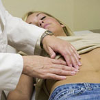 врач ощупывает живот пациента