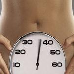 часы на фоне женского живота